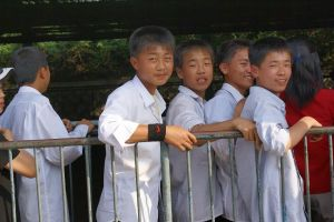 North Korean schoolboys stand in line, smiling nervously. (Photo by Ian Coppell)