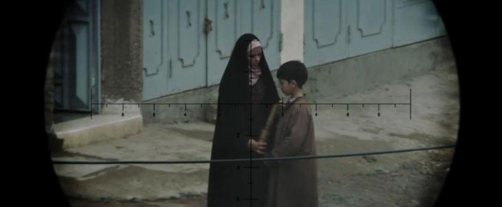 A scene from the movie showing a mother and her child holding a grenade