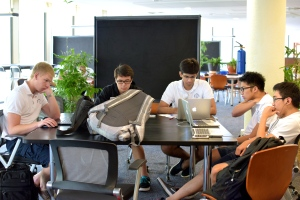 Kyle Chan (far right) enjoys studying with his peers in the library.  Photo by: Christopher Khoo