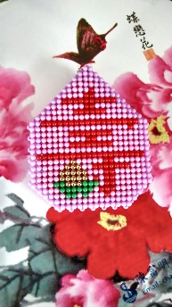 "Handicraft with the Chinese character meaning ""longevity."" Chinese painting of pink and red flowers in the background."