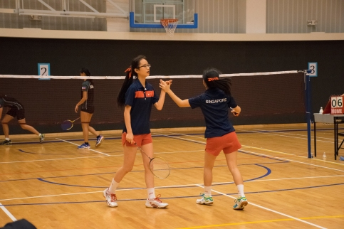 Yvonne Chien and Momoe Kubota high-fiving each other after winning a point. Photo by Ariel So.